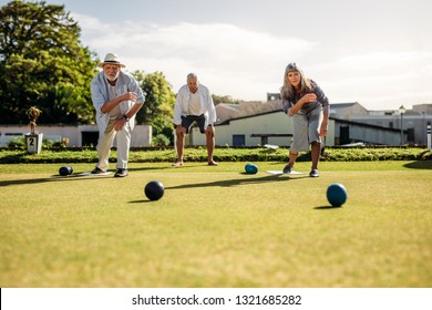 People playing a game of boules in a lawn on a sunny day. Two senior persons bending forward throwing boules competing with each other.