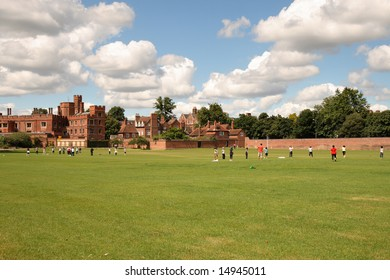People playing games in an English Park with Historic Eton School in the Background and white puffy clouds in the sky.