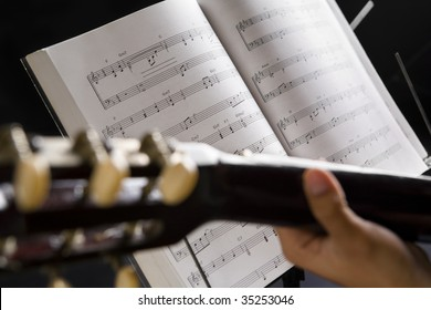 People playing guitar with musical chords in dark
