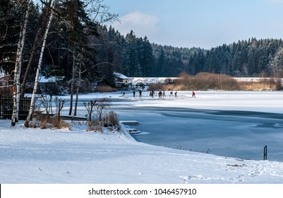 People playing ice hockey on pond