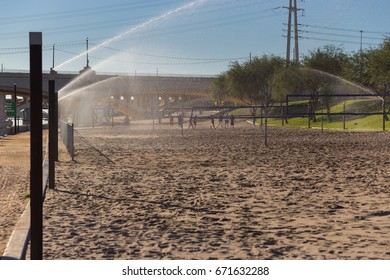 People Playing on a Sand Volleyball Court with Sprinklers Running, Arizona, USA, horizontal