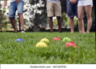 People playing petanque in a park, detail of balls, legs in background.