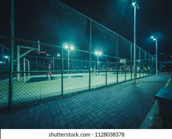 people playing soccer at night on sports field in city -