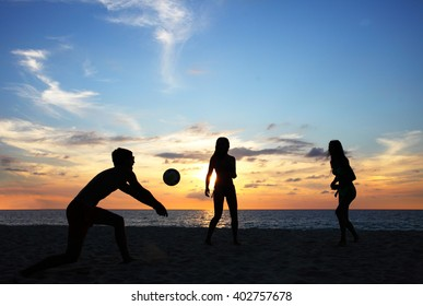 People playing volleyball on tropical sea beach at sunset