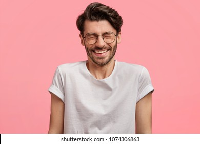 People and positive emotions concept. Delighted glad bearded male with stylish hairdo, dark beard, keeps eyes shut, smiles joyfully, dressed in casual white t shirt, isolated over pink background