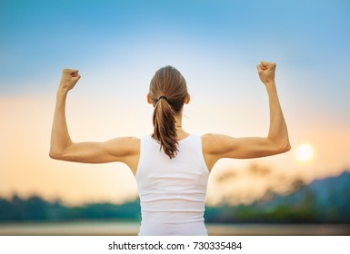 People, power, strength, and determination.  Strong woman flexing her muscles against sunset.