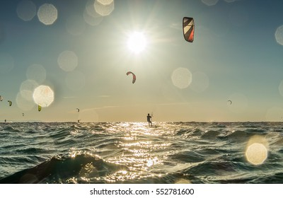People practicing kitesurf. Backlit image with bokeh in water drops on lens. Tarifa, Andalusia.