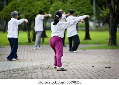 People practising tai chi in the park