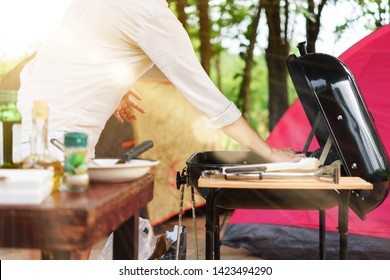 People praparing barbecue party with bbq stove and make tent for camping