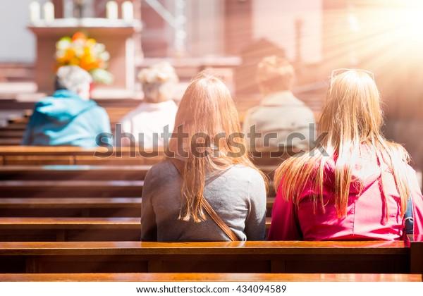 Personnes priant dans une église