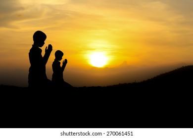 people  praying at the sunset.