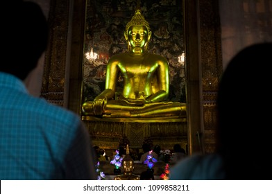 people praying at thai temple during buddhist holidays