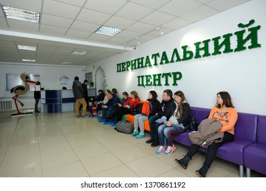 People, pregnant women and relatives, sitting in chairs waiting in a reception hall of a maternity hospital. City perinatal center. April 12, 2019. Kiev, Ukraine