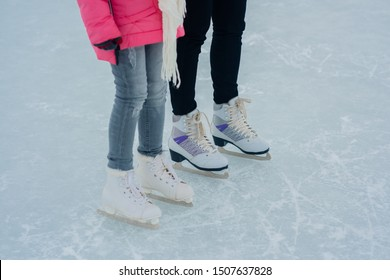 People are prepare going to go skating. mother helps her daughter to wear skates. Close up details legs