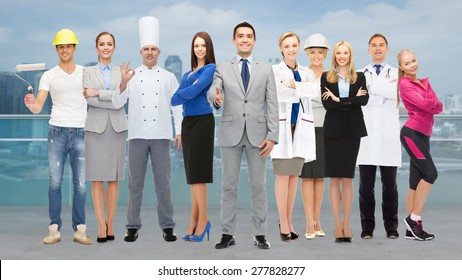 people, profession, qualification, employment and success concept - happy businessman with group of professional workers showing thumbs up over city background