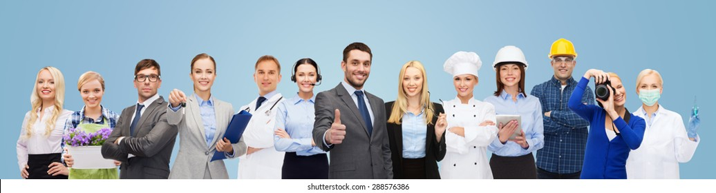 people, profession, qualification, employment and success concept - happy businessman over professional workers showing thumbs up over blue background