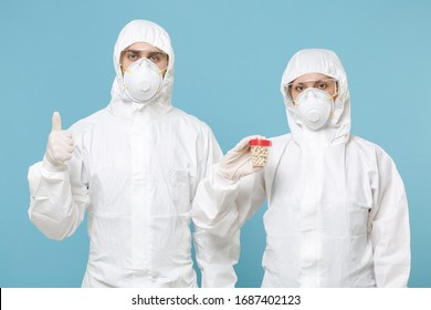 People in protective suits respirator masks hold drugs isolated on blue background studio. Epidemic pandemic new rapidly spreading coronavirus 2019-ncov from Wuhan China, medicine flu virus concept
