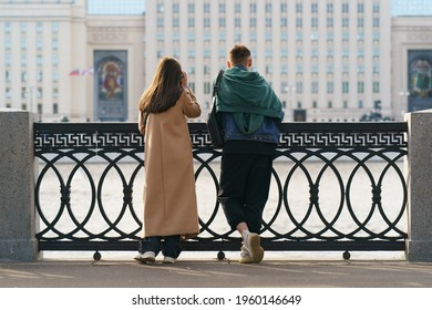People in the public park in spring day. Leisure theme. Couple of young man and woman looking at cityscape and Moskva river. Backs, rear view.