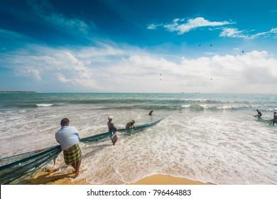 People pulling fishing net in Arugambey, Sri Lanka