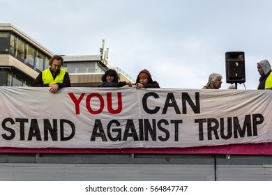 People put up anti Donald Trump banner. Stockholm, Sweden - January 21, 2017: Anti Donald Trump banner and people at demonstration in Stockholm January 21, 2017. People behind anti Donald Trump banner