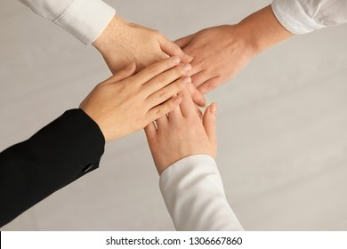 People putting hands together on light background