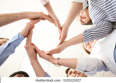 People putting their hands in circle on light background. Unity concept