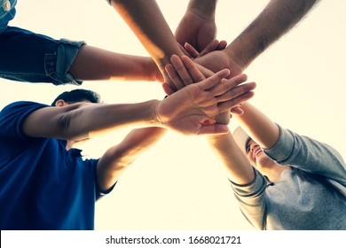 People putting their hands together. Friends with stack of hands showing unity and teamwork. Friendship happiness leisure partnership team concept.