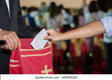 people putting tithing into Velvet offering bag in church