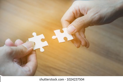 People putting two pieces of jigsaw together,Hands of business people hold paper jigsaw puzzle and solving puzzle together,Business team assembling Jigsaw puzzle,