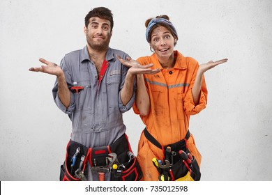 People, puzzlement, confusion concept. Young untidy hard working construction workers shrug shoulders in bewilderment, don`t know where to buy necessary material or equipment for bilduing new object