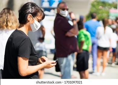Menschen, die sich mit einer Maske für Coronavirus in einer Warteschlange befinden,