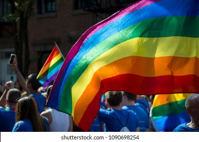 People with rainbows flags in the annual Gay Pride Parade as it passes through Greenwich Village.