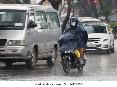 People with a raincoat ride on a motorbike in the rain. Transportation in the city when it rains.
