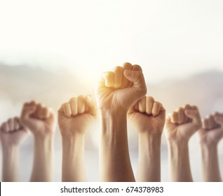 People raised fist air fighting for their rights with sunlight effect,  labor movement, election movement, copy space