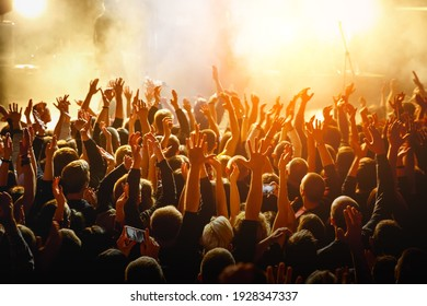People with raised hands at a public event. Gathering in concert hall - Shutterstock ID 1928347337