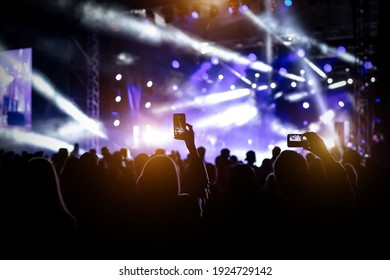 People with raised hands, silhouettes of concert crowd in front of bright stage lights