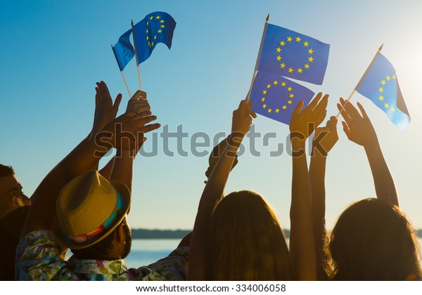 People with raised hands waving flags of the European Union. European dream. Future of Europe. European flag. Fans from Europe rooting for their team.