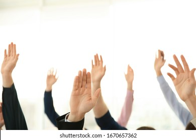 People raising hands to ask questions at business training on light background, closeup