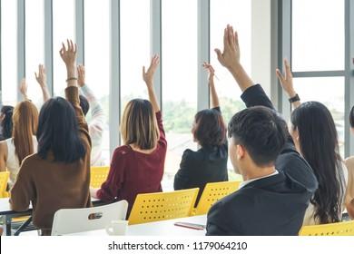 people raising hands during seminar.