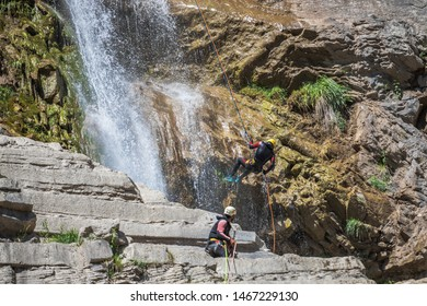people rappelling in an impressive waterfall between the mountains in Huesca, spain