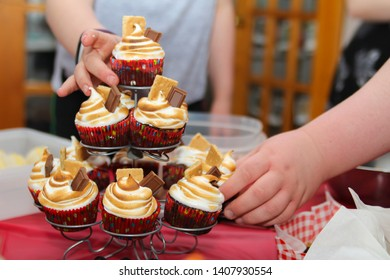 People reaching for cupcakes with torched meringue frosting at a party celebration