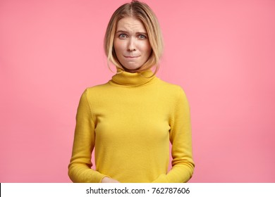 People, reactions concept. Confused hesitatnt female bites and presses lips in bewilderment, reacts on something, dressed casually, isolated over pink background. Worried woman expresses uncertainty