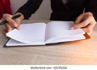 People ready writing on notebook on wooden table