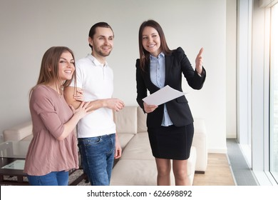 People and real estate. Young couple excited by lovely view from the window in luxury apartment for rent. Female realtor showing flat to clients telling about advantages, property for sale