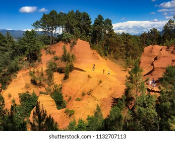 People in the red ochre landscape in the natural park near Roussillon, Provence, South of France