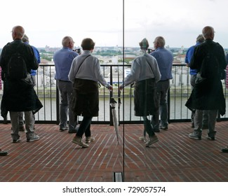 People reflecting in a facade on the observation deck of the Elbphilharmonie building in Hamburg, Germany, on July 21, 2017