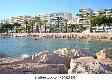 People relax on beach in city, view from rocky pier in Cannes, France