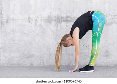 People, relax and sport exercises concept. Beautiful sporty female practices yoga, touches floor with hands, has healthy slim body, active fitness training, stands against concrete background