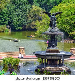 People relaxing and enjoying  a sunny day in Central Park at  Bethesda fountain. Free time leisure and travel concept. New York City. United States.