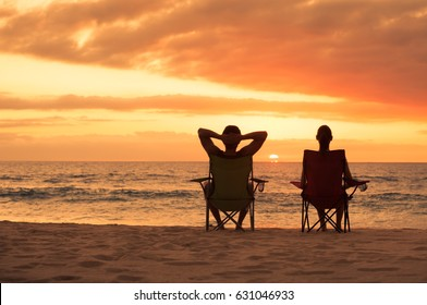 People relaxing moment's. Man and woman enjoying a sunset a the beach.